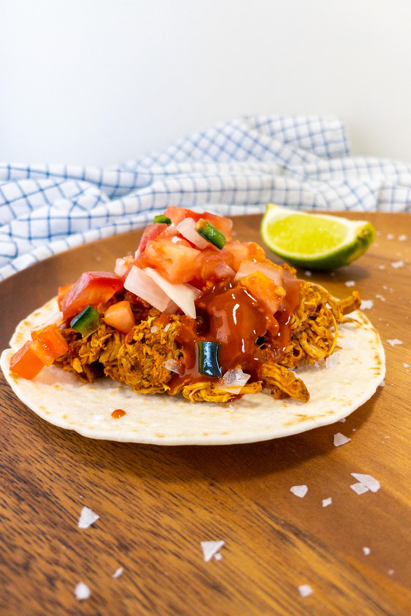 Mexicaans recept voor taco's met pollo pibil op een houten ondergrond. Daarbij limoenen en zout