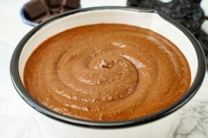 Mole in een pan met daarachter chocolade en pepers