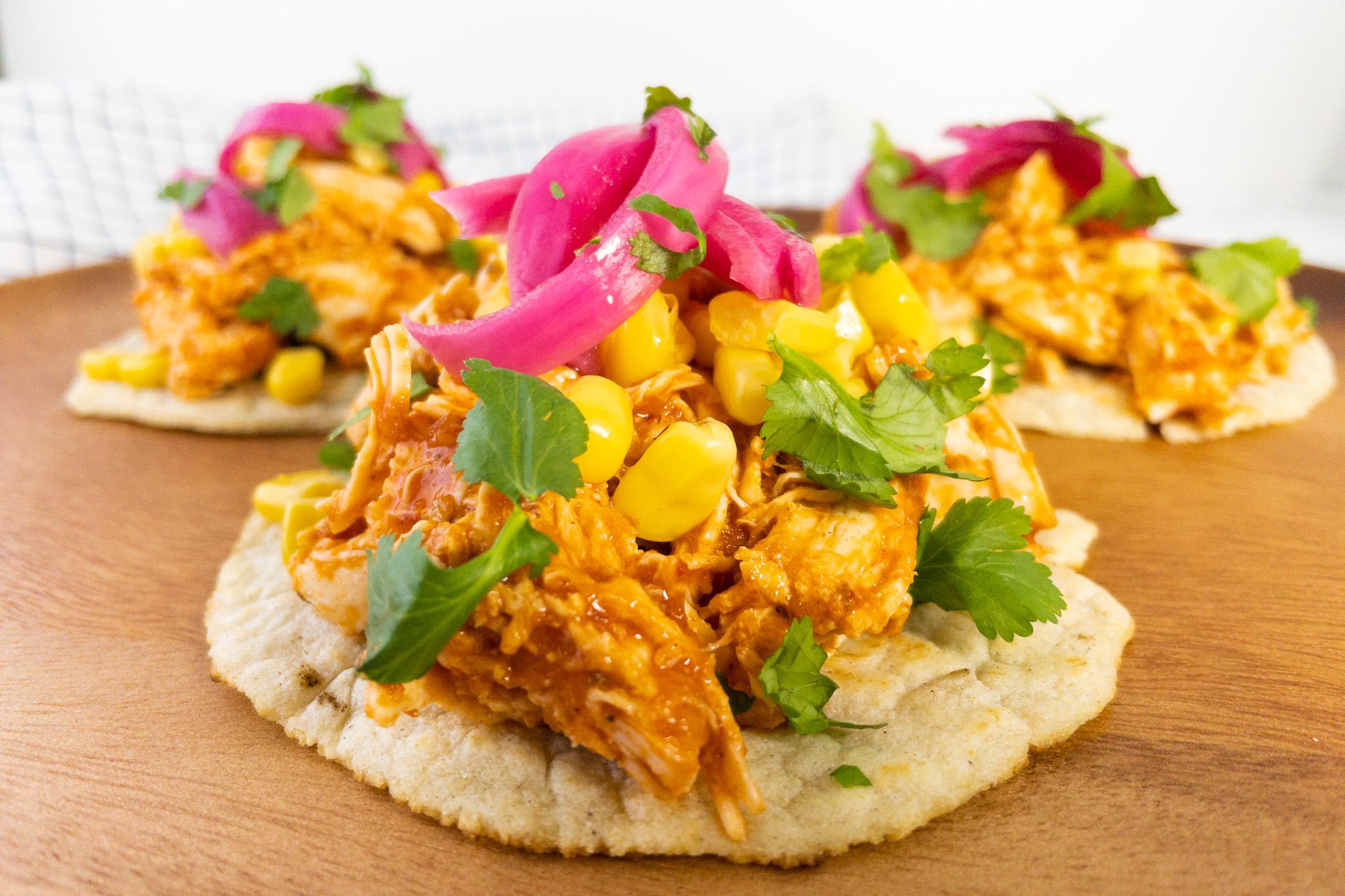 Een taco met kip, rode simpele enchilada saus, rode ingelegde ui en koriander