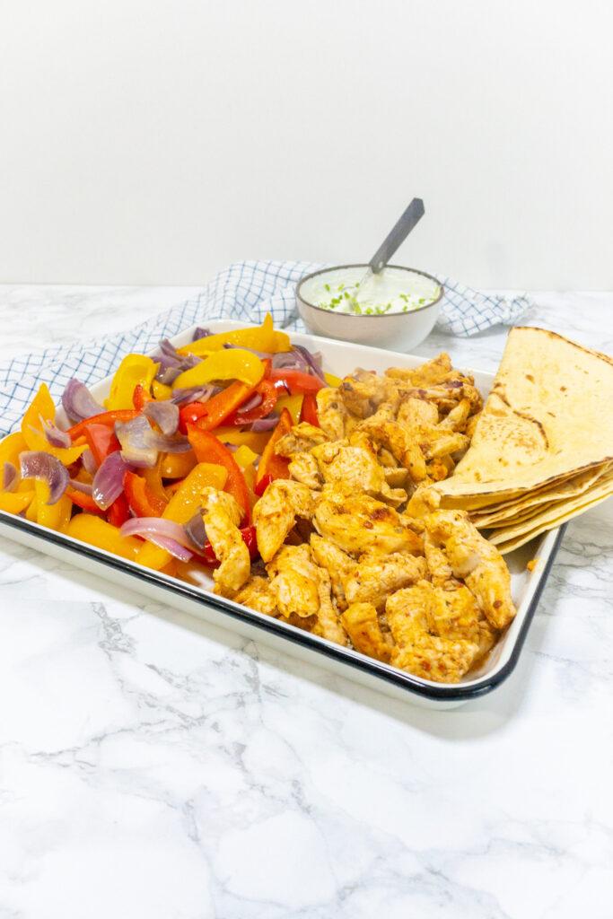 Mexicaans recept voor simpele Fajitas. Je ziet een plaat met daarop de groenten, kip en tortilla's. Daarnaast staat een bakje met de saus