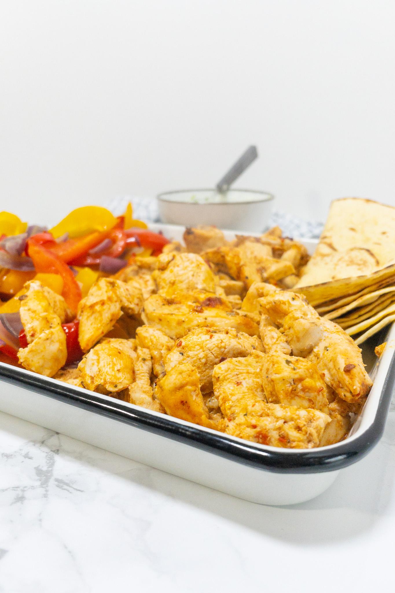 Mexicaans recept voor simpele fajitas, je ziet een ingezoomd beeld van de kip, groenten en tortilla's.