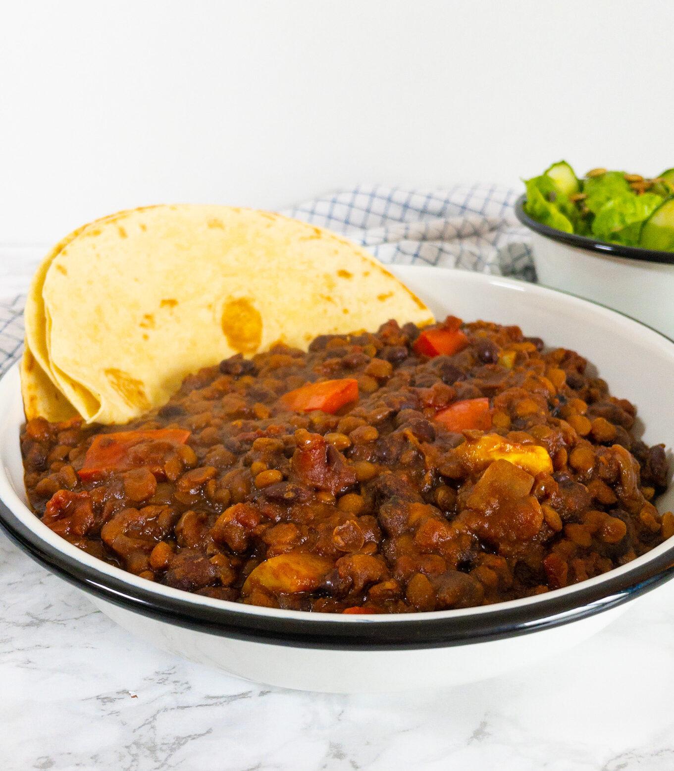 Mexicaans recept Chili sin Carne, je ziet een bord met daarop de chili sin carne. Daarachter staat een bakje met de salade.