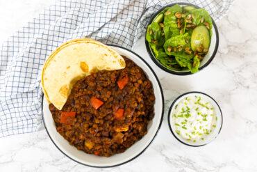 Mexicaans recept voor chili sin carne. Je ziet een bord met daarin de chili en tortilla's. Daarnaast staat een bakje salade én een bakje met de saus.